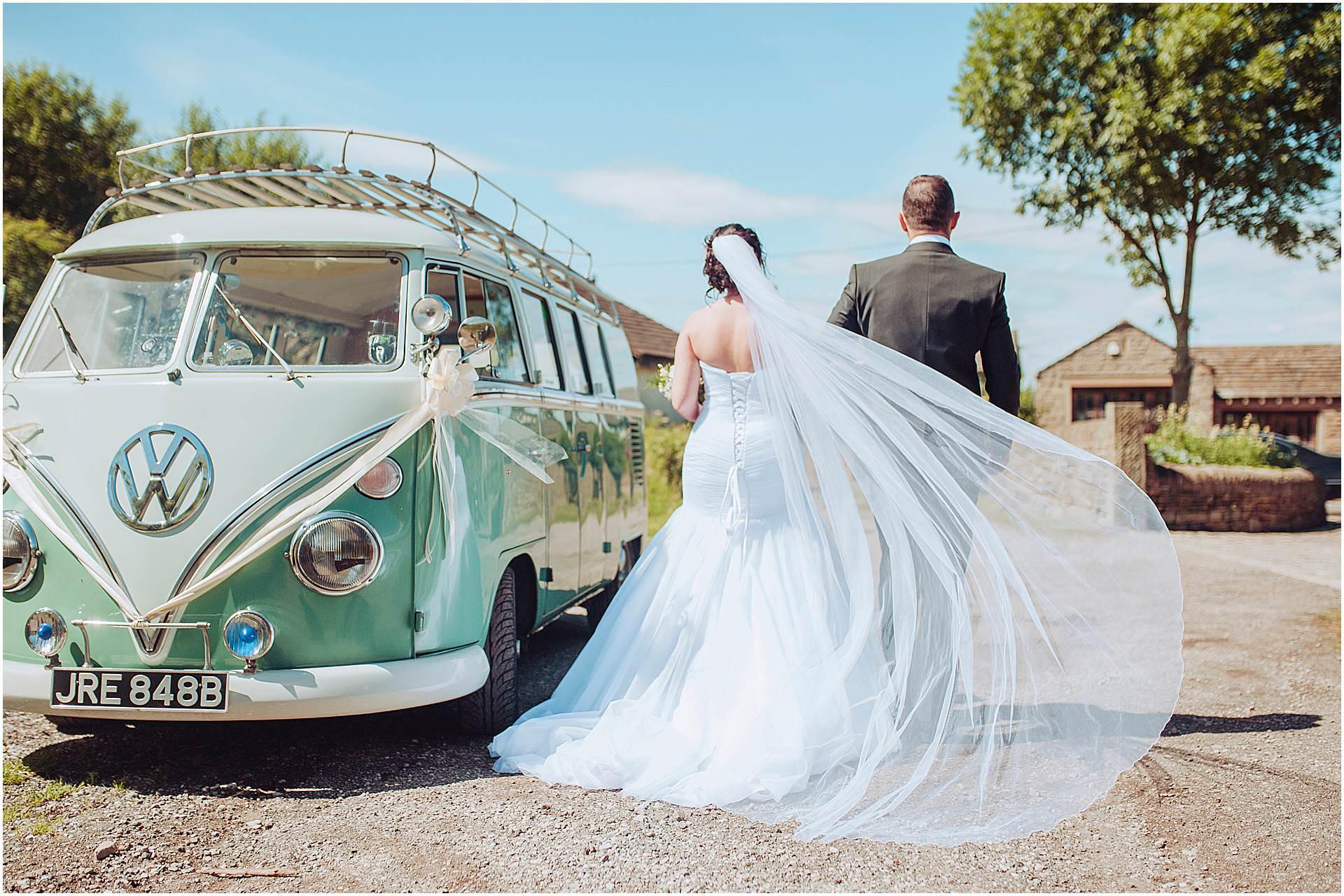bride and groom walking along side of their campervan