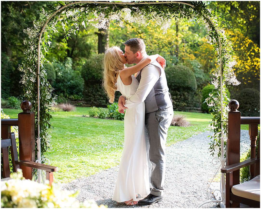 Bride and groom kissing under the pergola
