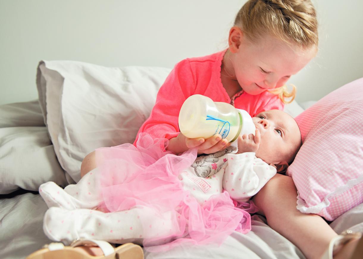 big sister feeding baby girl