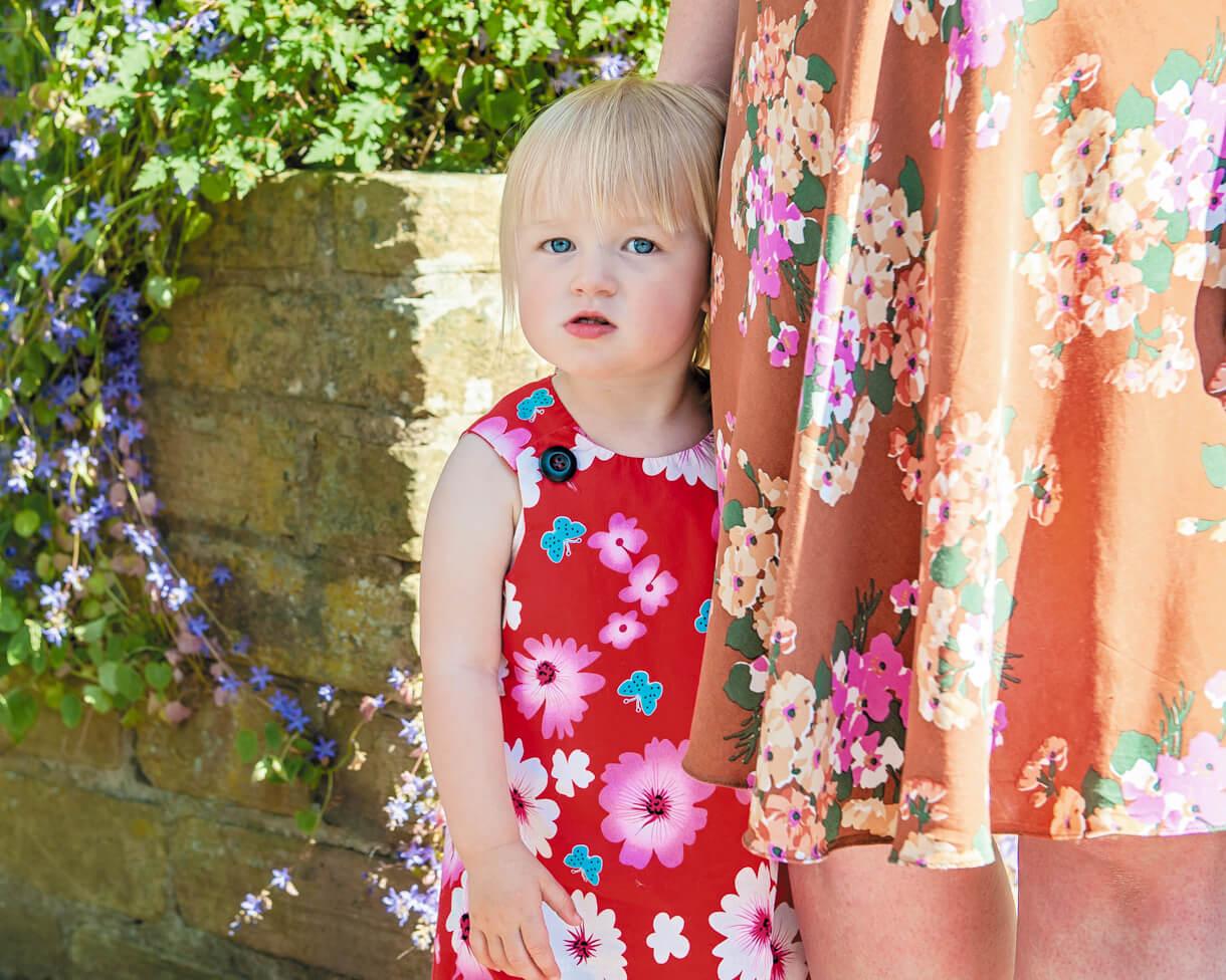 little girl hinding behind her mum's pretty skirt