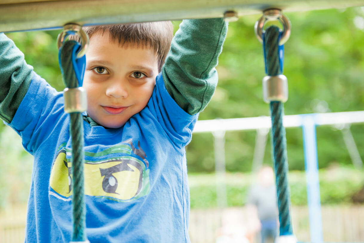young boy climbing on the climbing frame