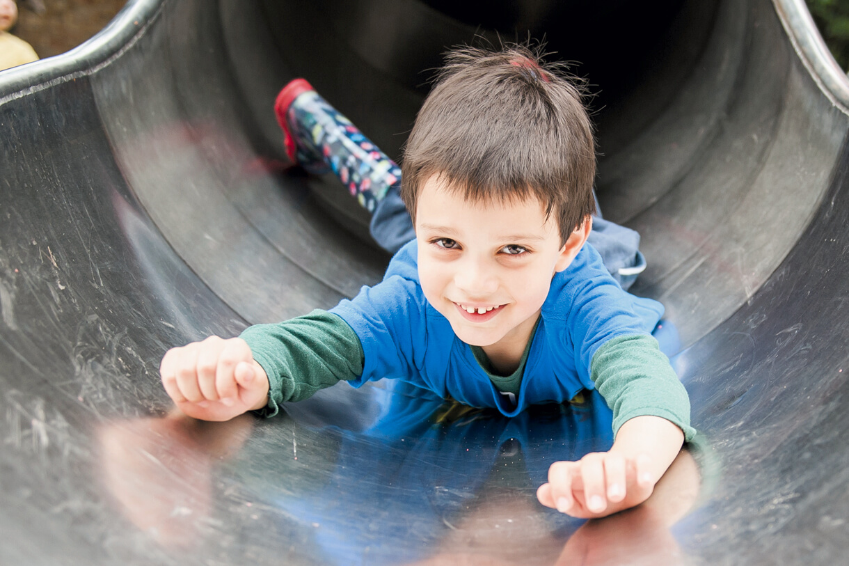 Boy coming down the large slide on his tummy