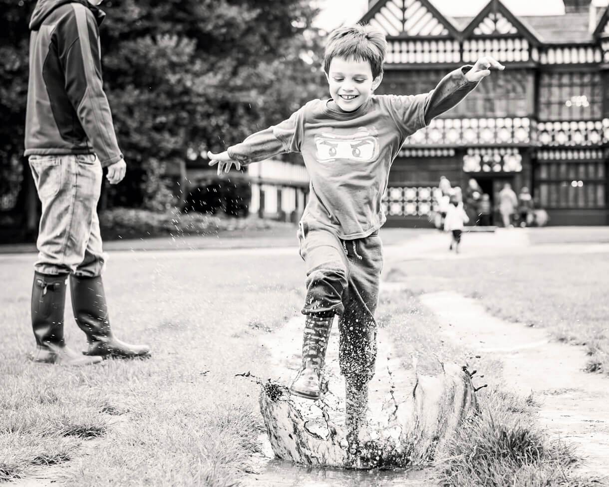 Little boy running in the mud