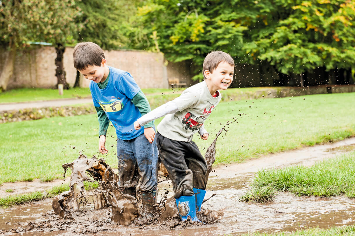 Little boys splashing in the muddy puddle