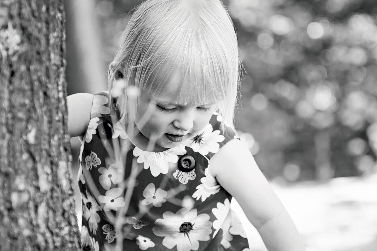 black and white shot of little girl picking flowers