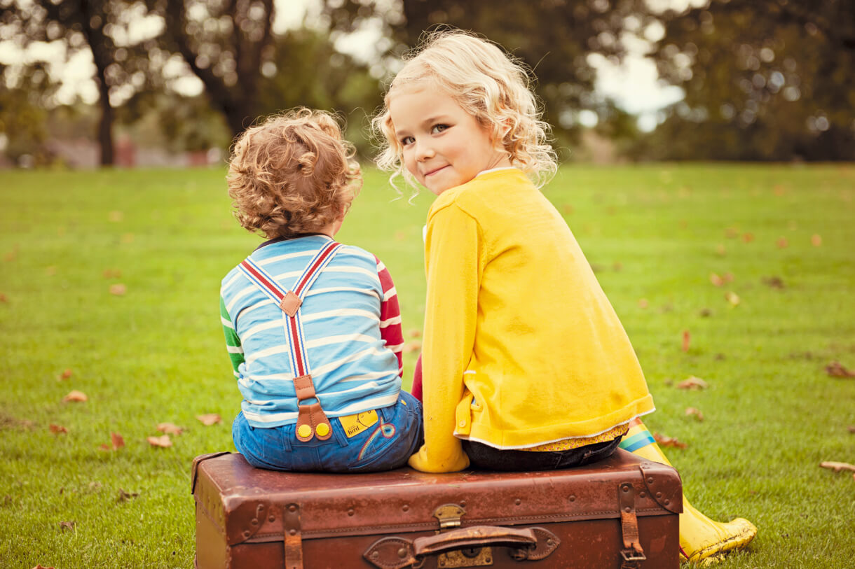 siblings sat on a vintage suitcase in the park