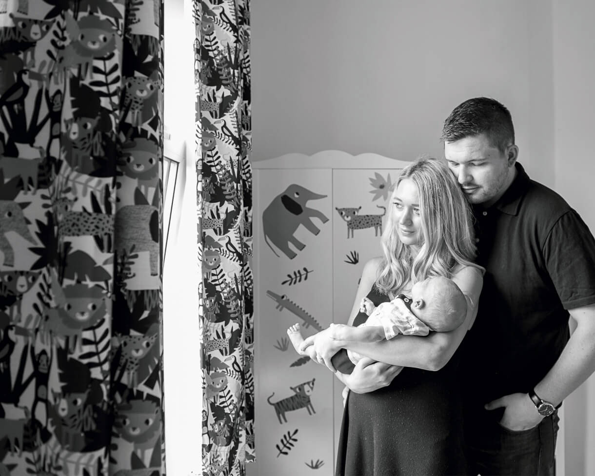 black and white image of mum and dad looking through the window with baby