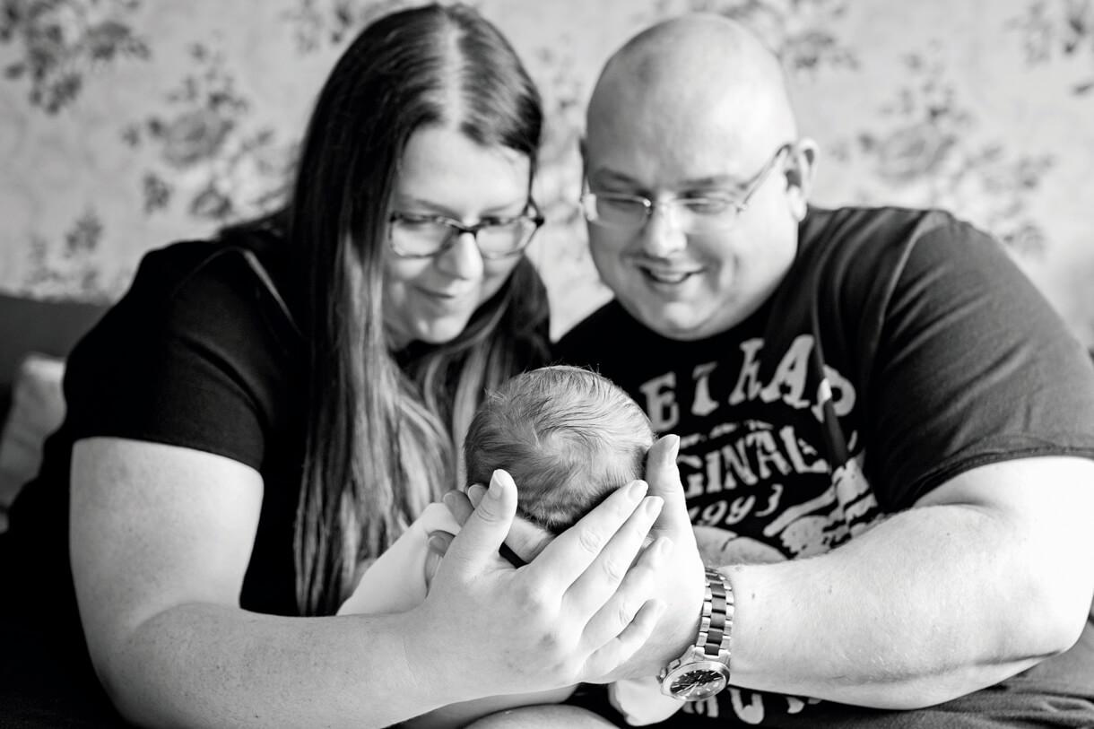 mum and dad smiling at baby boy