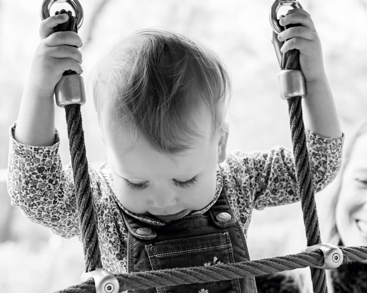 Little girl climbing up the climbing frame in Bramhall Park