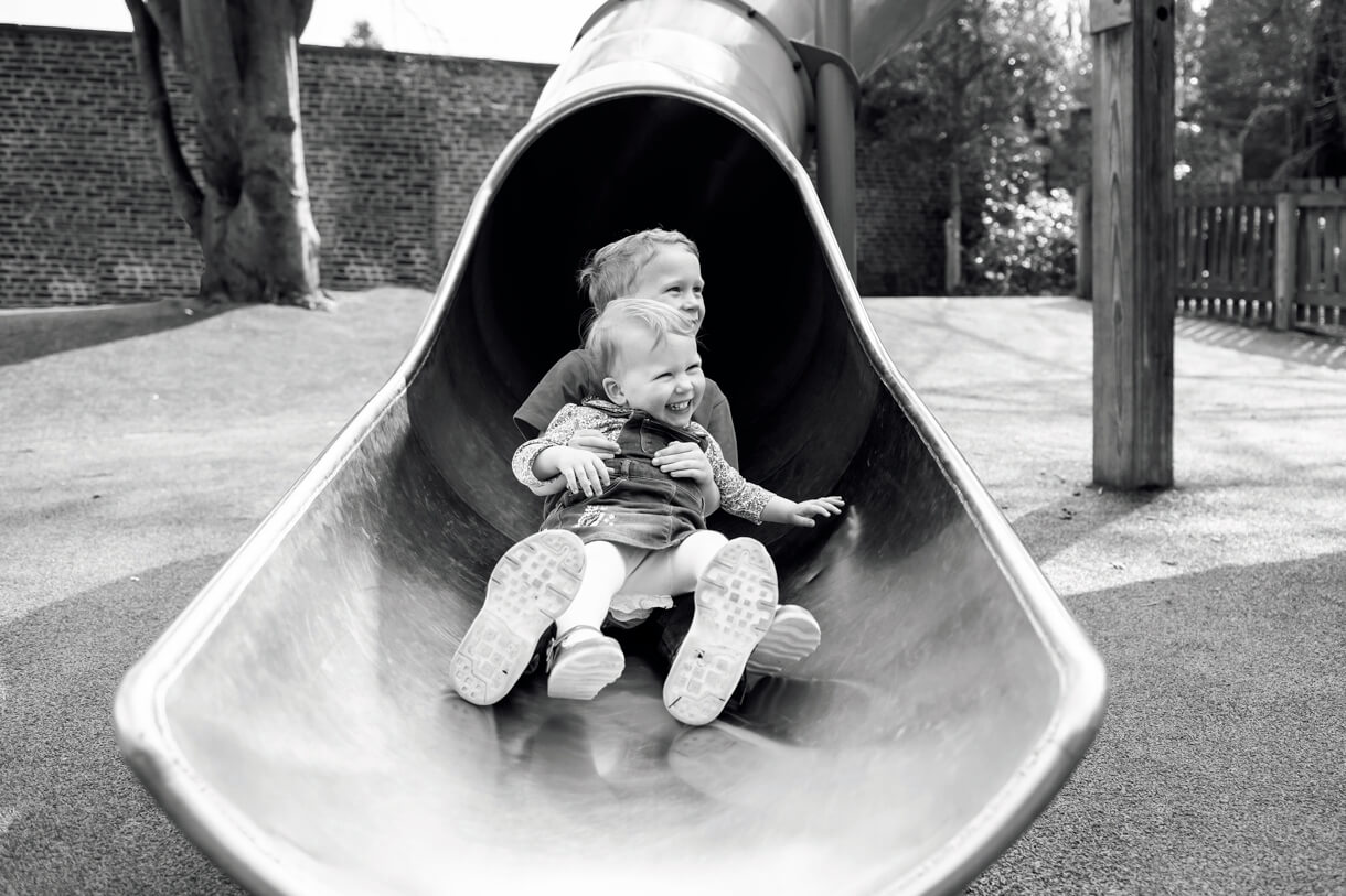 siblings coming down the slide at Bramhall hall park