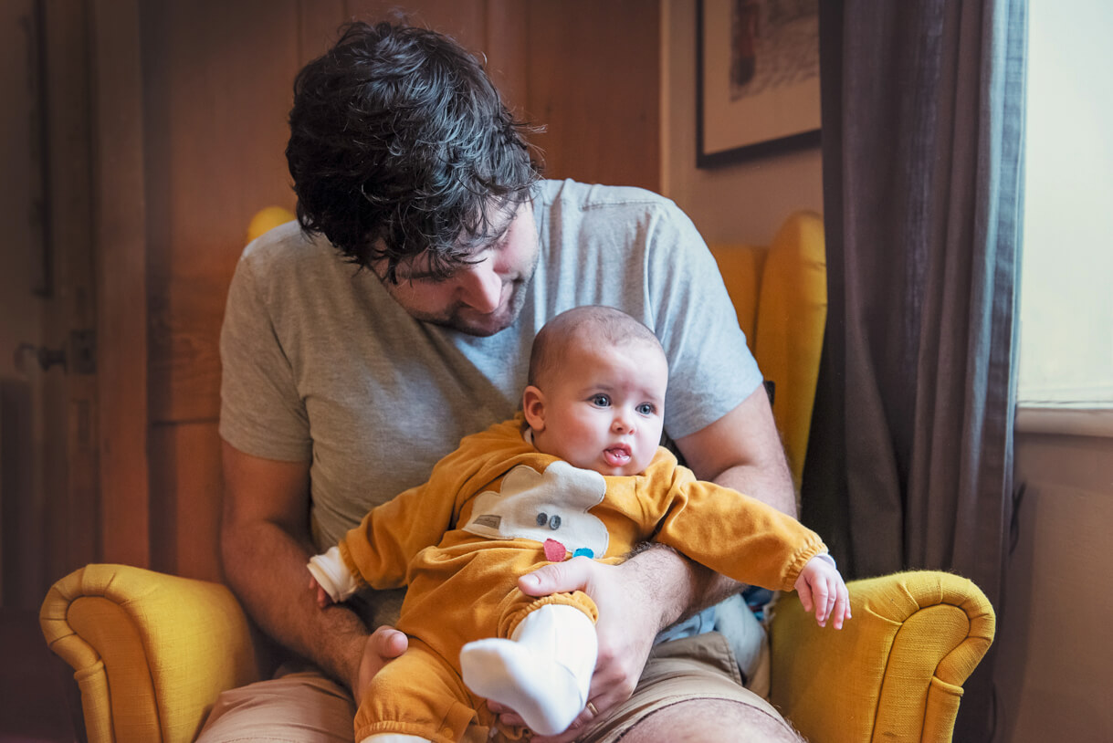 dad sat on yellow chair cuddling baby