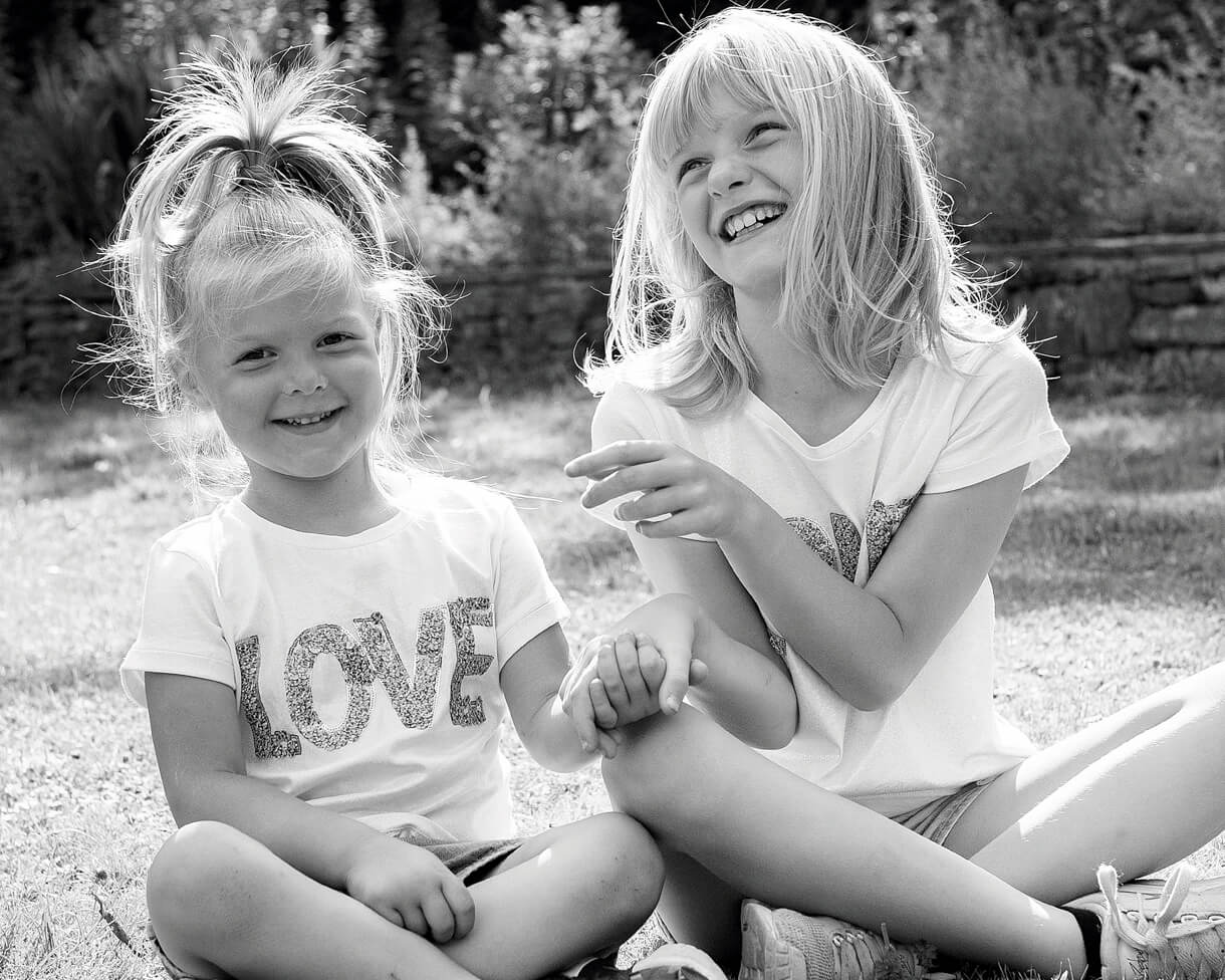 Sisters sat laughing in the park