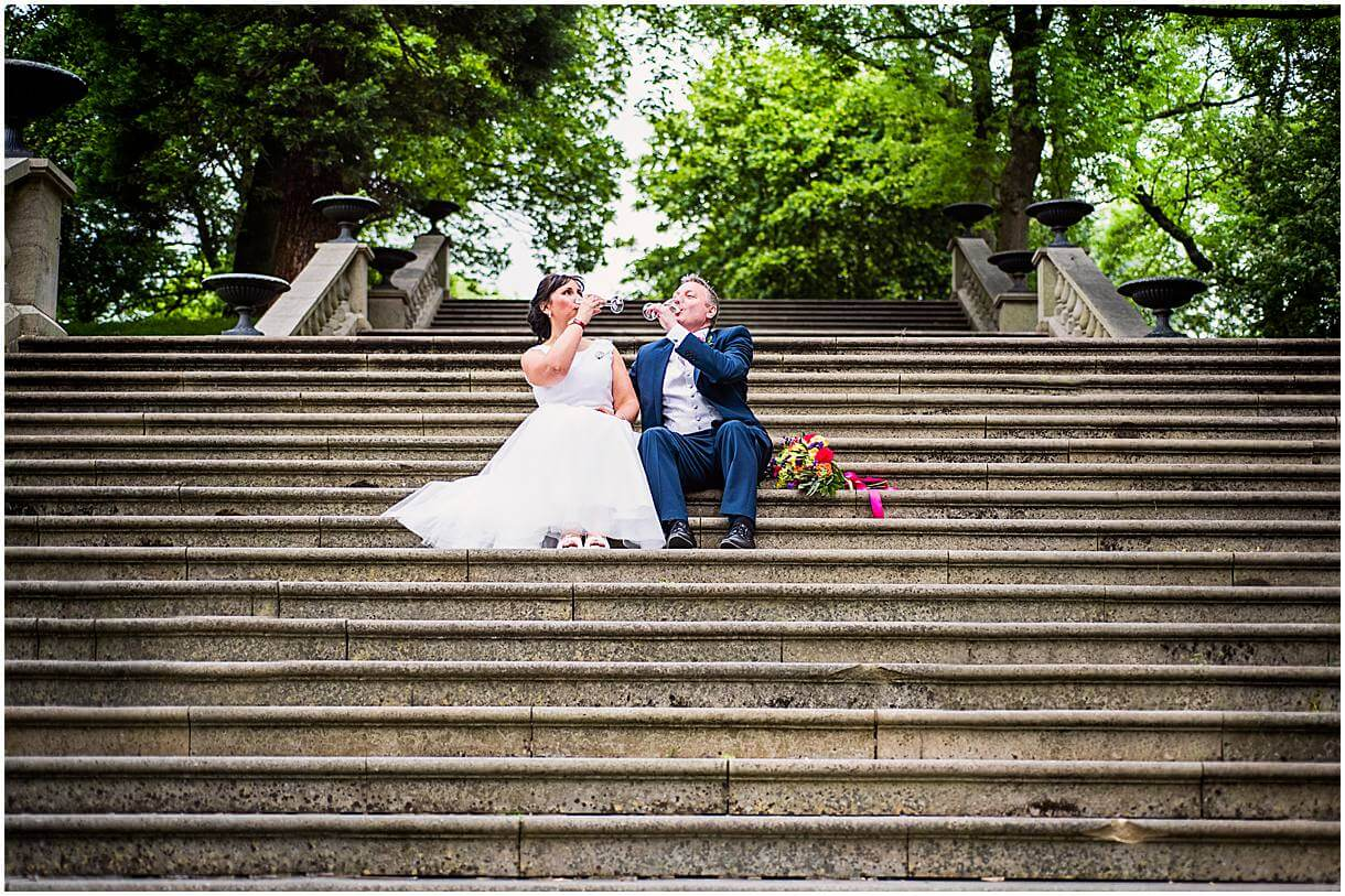 Bride and Groom sat on the steps of Dukinfield Park