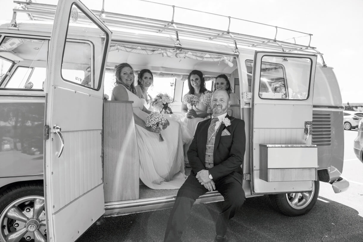 Bride and bridesmaids plus father of the bride sat with the wedding campervan