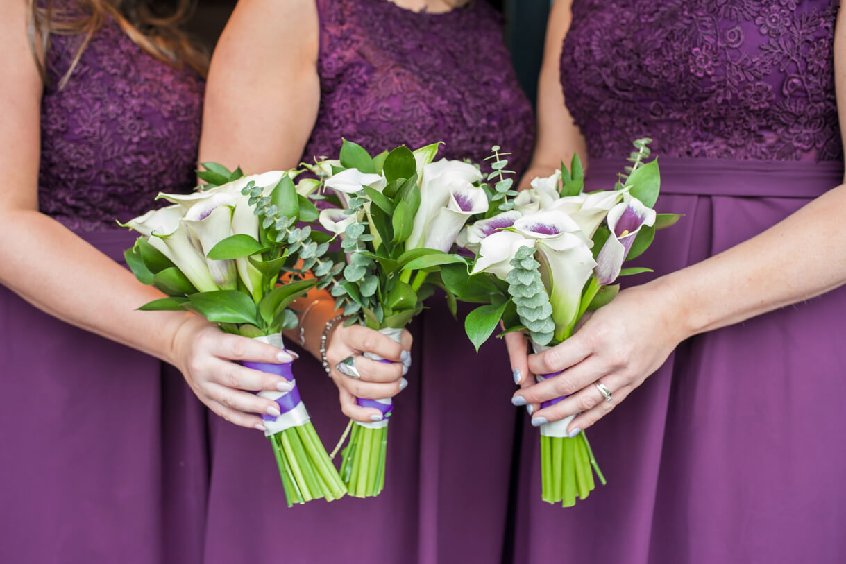 Bridesmaids in purple holding their bouquets